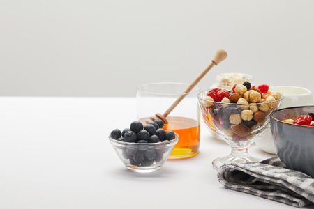 muesli with berries, nuts and honey served for breakfast on white table isolated on grey 写真素材