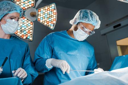 Krankenschwester und Chirurg in Uniformen und medizinischen Masken bei der Operation