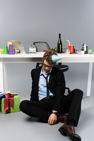 drunk businessman in party cap sleeping at messy workplace near presents