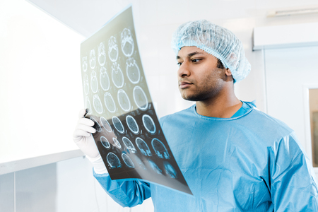 Handsome doctor in medical cap and uniform holding and looking at x-ray