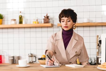 Hübsche, konzentrierte Geschäftsfrau, die an der Bartheke steht
