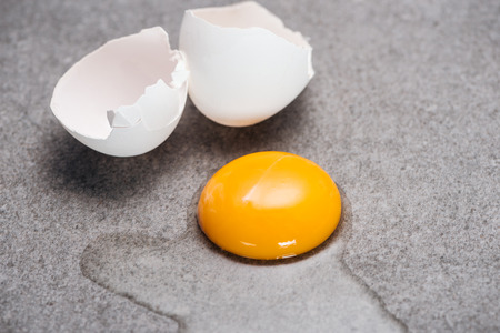Close up of raw smashed egg with yolk and protein on grey textured background