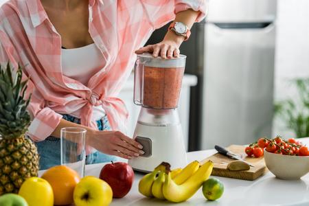 Vista recortada de la mujer preparando un delicioso batido en la licuadora Foto de archivo