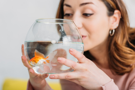 beautiful young woman holding fish bowl with bright golden fish