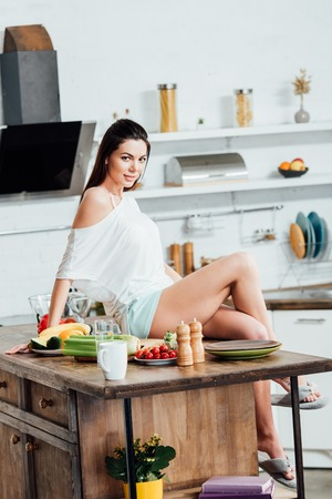 Pretty girl sitting on wooden table and looking at camera in kitchen Stock Photo
