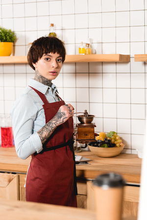 selective focus of pretty barista in apron holding coffee mill and looking at camera Banque d'images - 120984059
