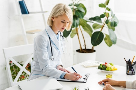 attractive blonde nutritionist in white coat writing diagnosis near patient Stock Photo