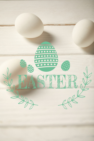 chicken eggs on white wooden table with turquoise Easter lettering Imagens