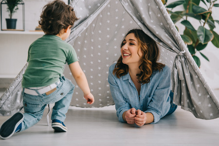 Smiling mother and son in grey wigwam at home