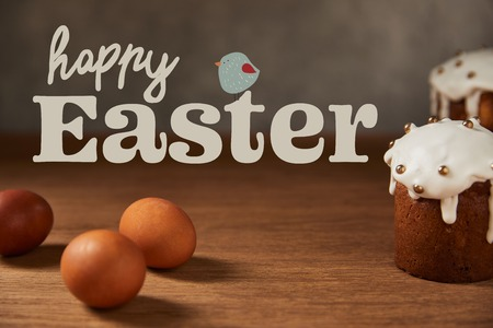 selective focus of traditional Easter cakes and chicken eggs on wooden table with happy easter lettering and bird illustration 版權商用圖片