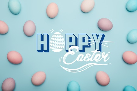 top view of painted colorful eggs on blue background with happy Easter lettering