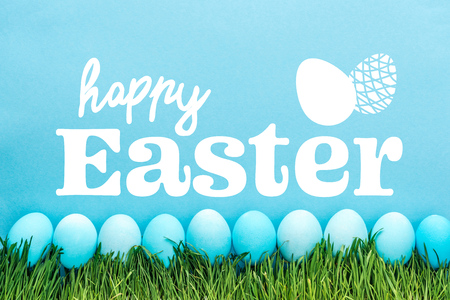 blue painted chicken eggs on green grass with happy Easter white lettering on blue background
