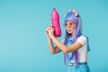 Asian anime girl in wig and glasses holding water gun isolated on blue Stock Photo