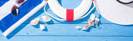 panoramic shot of striped towel, sunglasses, lifebuoy, white floppy hat and seashells on blue wooden background
