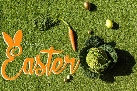top view of carrot, savoy cabbage and painted Easter eggs on green grass with happy Easter lettering