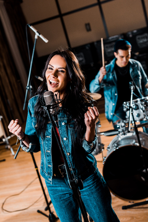 selective focus of beautiful emotional woman singing while mixed race musician playing drums in recording studio 写真素材