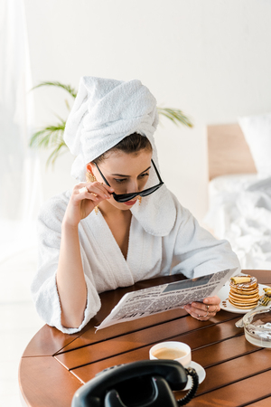 woman in bathrobe, sunglasses and jewelry with towel on head reading newspaper at morning Banco de Imagens - 121449806
