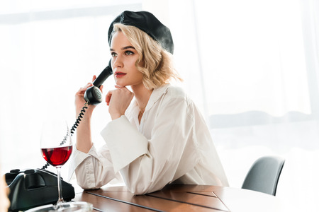 elegant blonde woman in black beret and white shirt sitting at table and talking o retro phone near glass with red wine on table