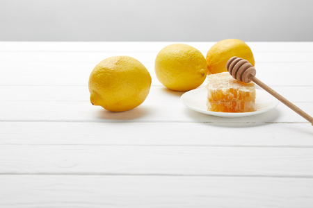 delicious honeycomb, lemons and honey dripper on white wooden table isolated on grey
