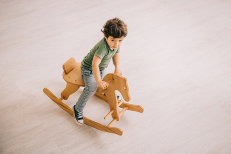 overhead view of little boy in green t-shirt riding on rocking horse Stock Photo