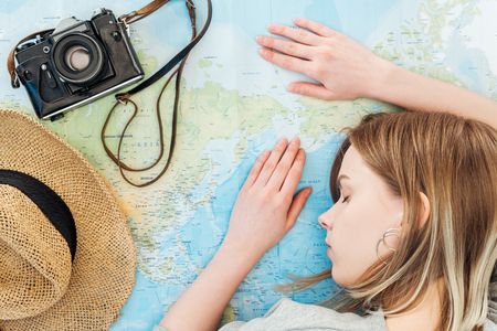 Woman with film camera and straw hat sleeping on world map