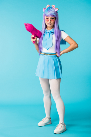 Full length view of asian anime girl in wig and glasses holding water gun on blue