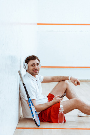 Smiling squash player listening music in headphones and using smartphone