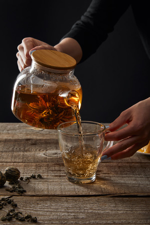 cropped view of young woman pouring blooming tea from teapot in cup isolated on black