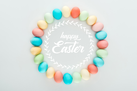 top view of round frame made of painted multicolored eggs with happy Easter white lettering