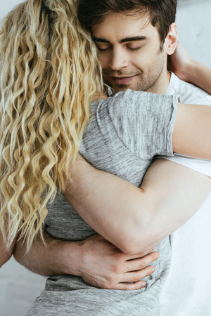 back view of blonde girl hugging with happy boyfriend with closed eyes