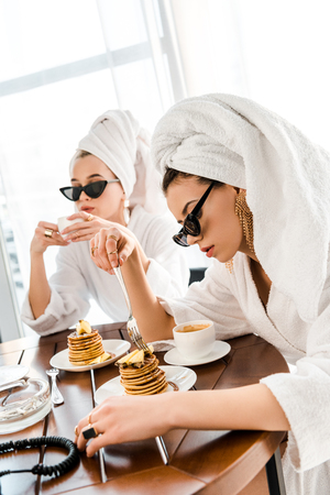 stylish women in bathrobes, sunglasses and jewelry with towels on heads eating pancakes for breakfast