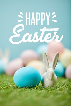 blue painted egg near decorative bunny on green grass with happy Easter lettering above Imagens