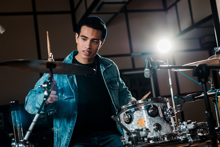 handsome mixed race musician playing drums in dark recording studio Фото со стока