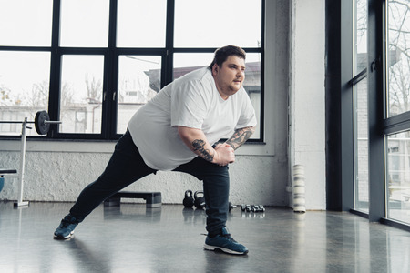 overweight tattooed man stretching legs at sports center 스톡 콘텐츠
