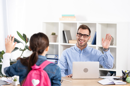 selective focus of happy father waving hand while looking at daughter in office