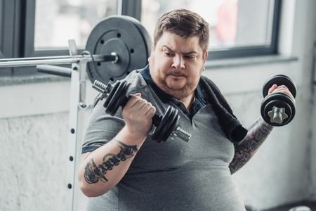 Obese tattooed man exercising with dumbbells at sports center
