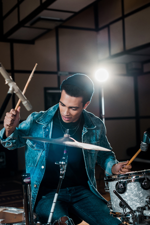 good-looking, inspired mixed race musician playing drums in recording studio