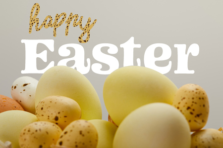 yellow painted eggs with happy Easter lettering on grey background Фото со стока