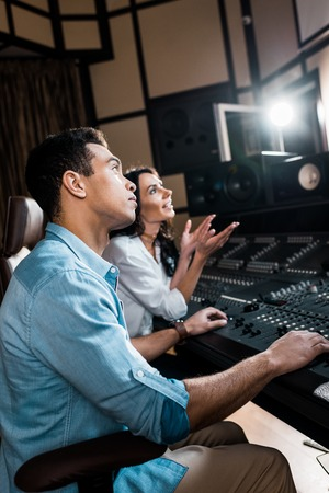 selective focus of sound producers working at mixing console in recording studio Foto de archivo - 121450534