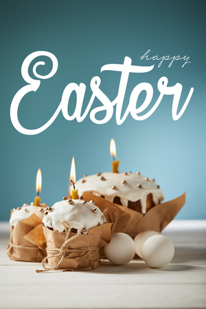 traditional Easter cakes in craft paper with burning candles and white chicken eggs on blue background with happy easter lettering Stock Photo