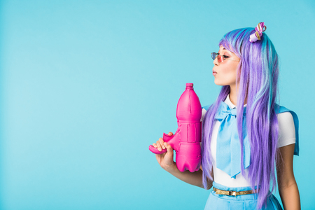 Asian anime girl in wig and glasses holding water gun isolated on blue Stock fotó