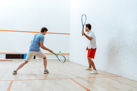 Full length view of two sportsmen playing squash in four-walled court Stock fotó
