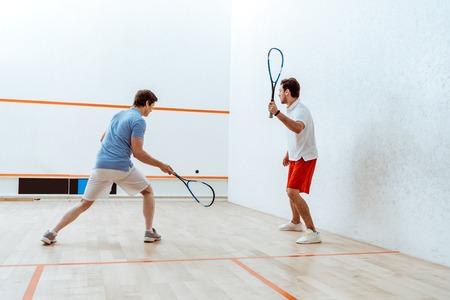 Vue sur toute la longueur de deux sportifs jouant au squash dans une cour à quatre murs Banque d'images