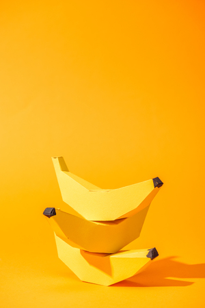 yellow paper bananas on orange with copy space Фото со стока