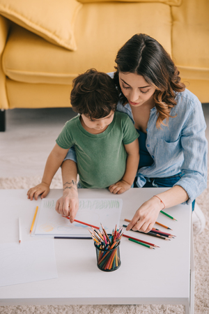 Mother and son drawing with color pencils in living room Stock Photo