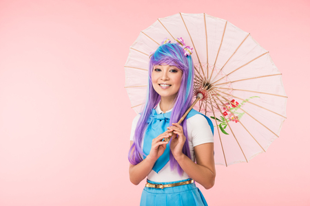 Smiling asian anime girl in wig holding paper umbrella isolated on pink