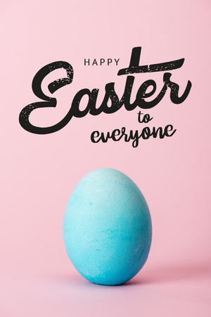 blue chicken egg on pink background with happy Easter to everyone lettering Standard-Bild - 121450929