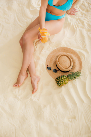 top view of girl in bikini with cocktail, Straw Hat, Pineapple and sunglasses on beach