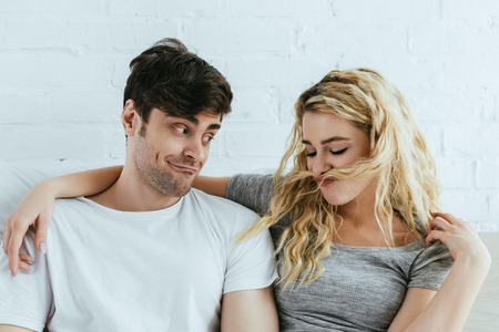 handsome man looking at girl with blonde hair on face