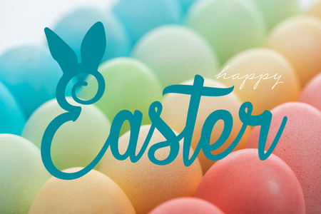 happy Easter lettering on background of multicolored painted eggs